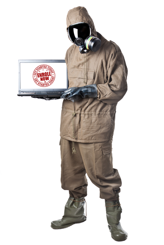 Worker in hazmat suit holding a laptop